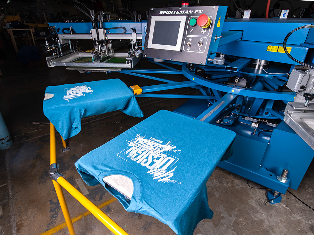 "An automatic screen printing press loaded with freshly printed custom t-shirts showing off a ""You design t-shirts"" slogan."