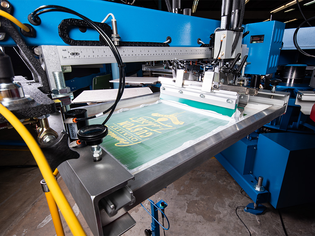 A close up image showing one print head on an automatic screen printing machine just after printing a new custom design.