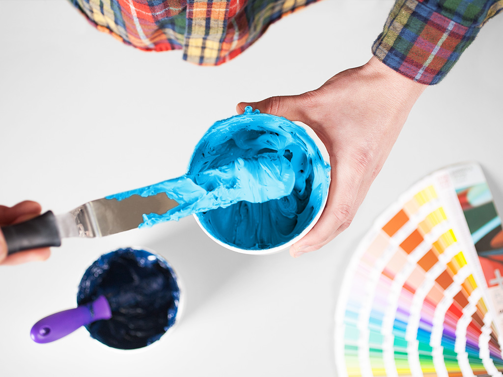 Mixing screen printing ink by hand with a spatula while using our Pantone color matching book.