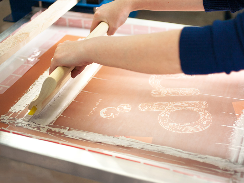 An UberPrints printer pulling a squeegee to print the first white ink color on our custom UP design.