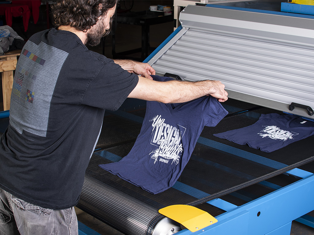 A screen print operator laying completed prints on the belt dryer to cure the wet ink.