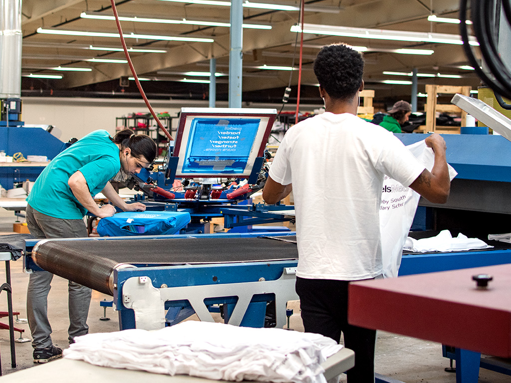 A view from inside the UberPrints screen printing production facility with press operators printing and inspecting custom t-shirt orders.