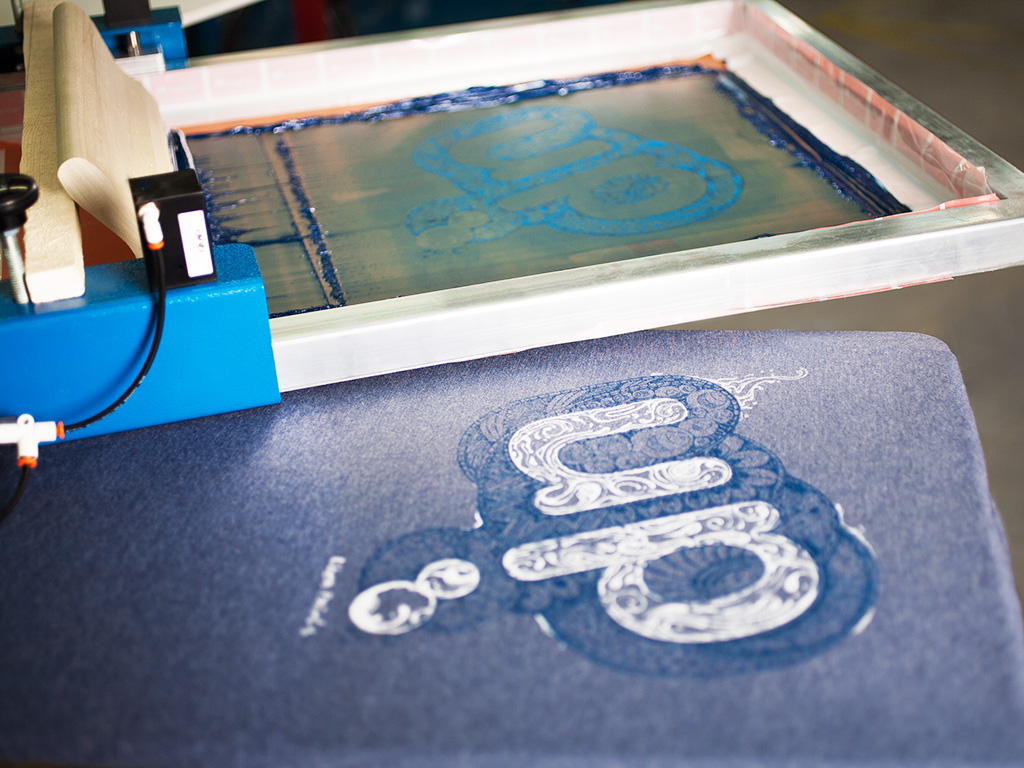 The custom UP design just after the second blue ink color was printed on our manual screen printing press.