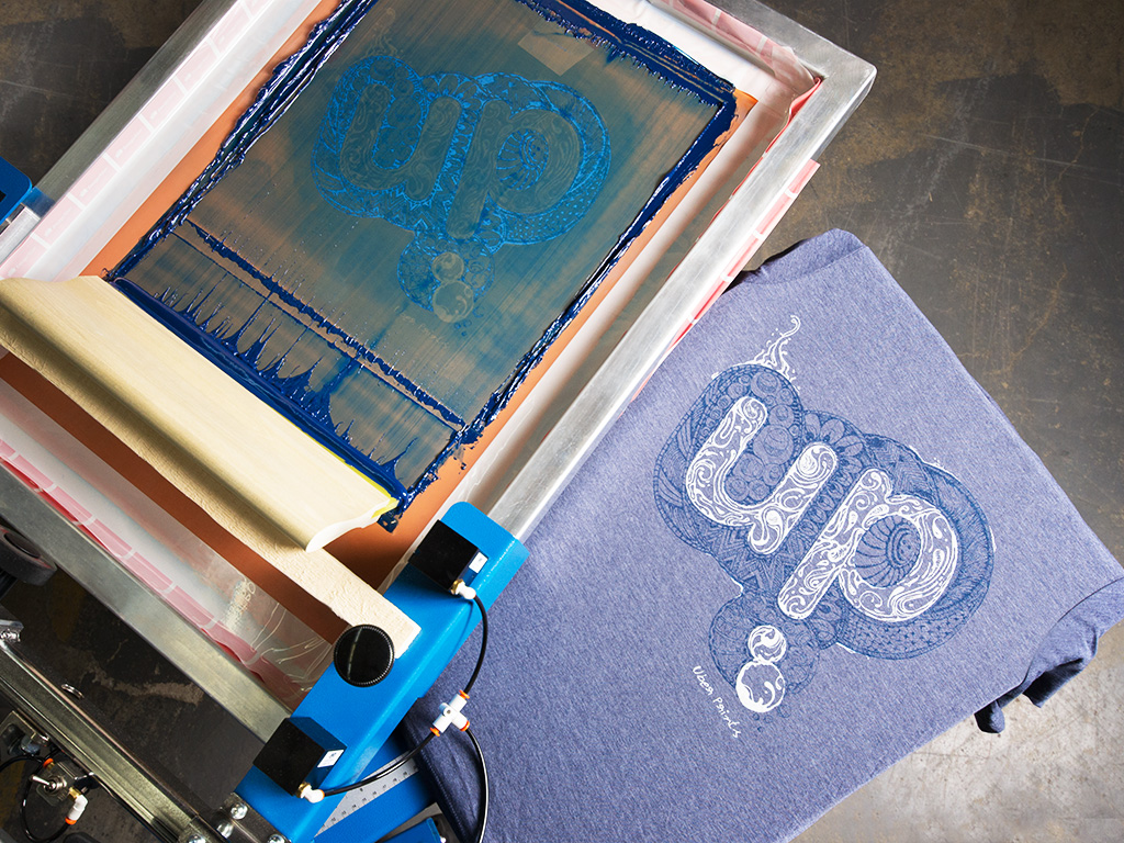 A manual screen printing press with an UberPrints design freshly printed on a t-shirt.