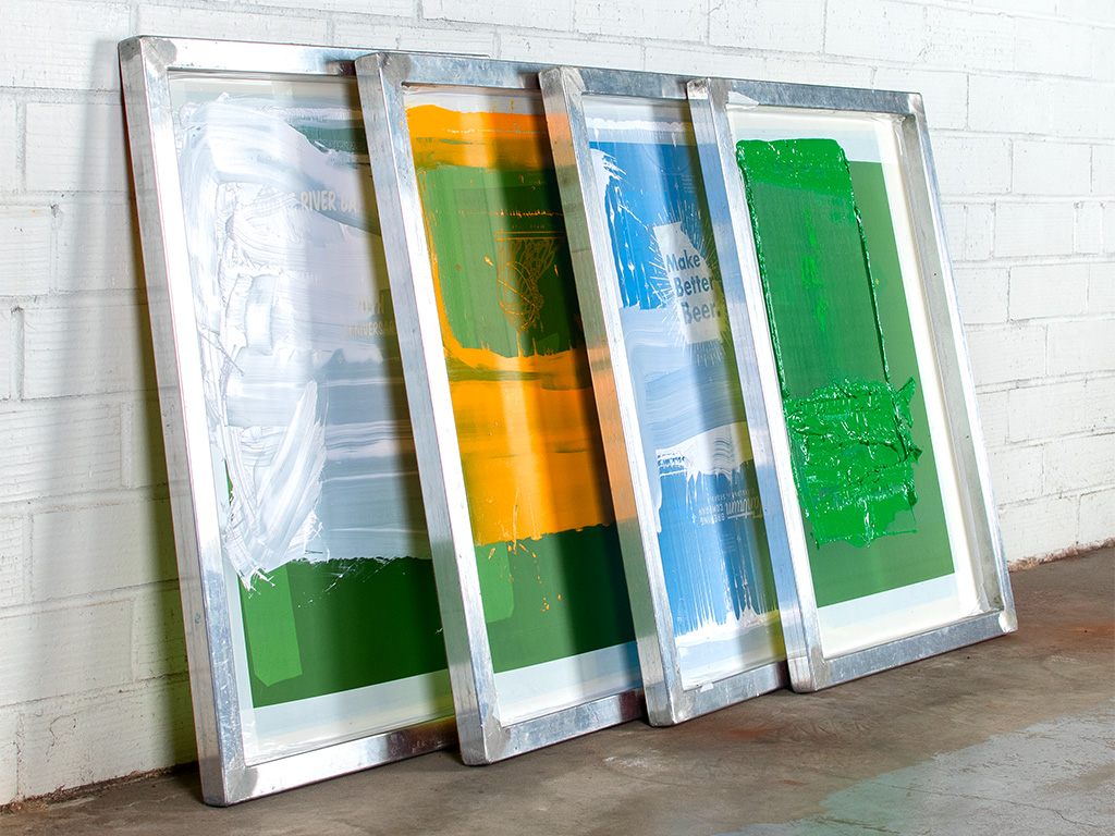 Four screens stacked against the production warehouse wall after being used to print our custom t-shirt orders.