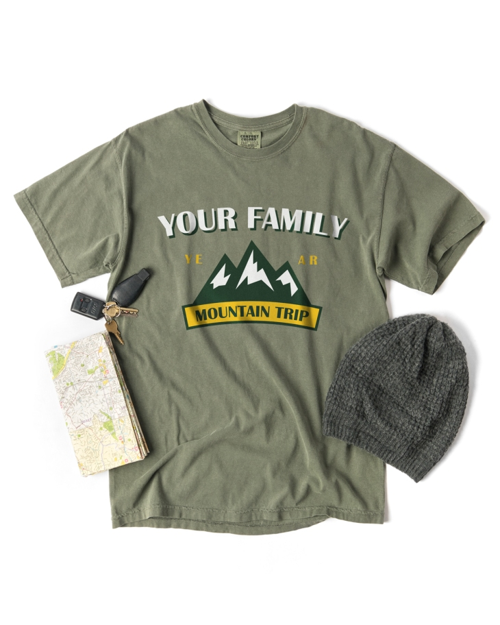 Pigment Dyed Tee by Comfort Colors in the color hemp shown with a family vacation design template and other road trip props.