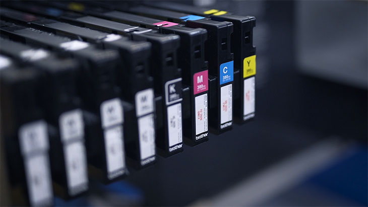 Showcasing the CMYK ink cartridges of a direct-to-garment printer.