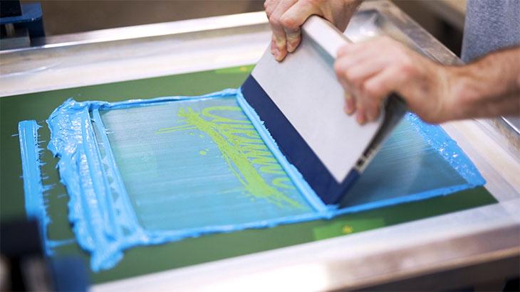 Screen print press operator demonstrating the printing stroke.
